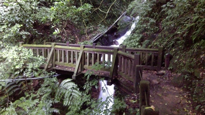 bridge crossing in front of a small waterfall