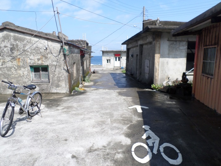 bike trail cutting through a small, run-down fishing village