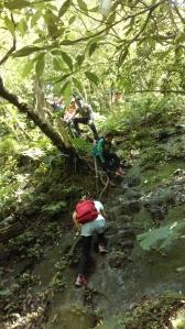 climbing past a small waterfall